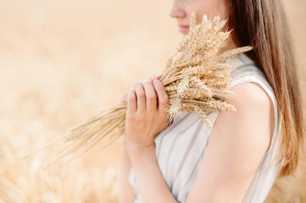 Menina segurando uma espiga dourada de trigo em um campo de trigo. mulher segura trigo com as duas mãos. Foto Premium
