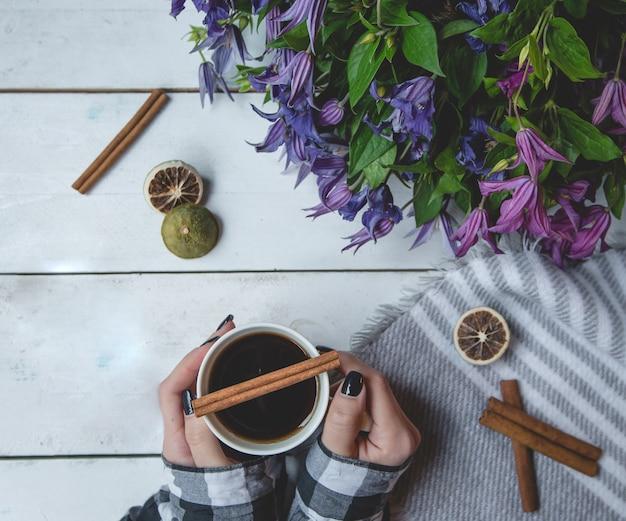 Menina, segurando uma xícara de chá com canela e margarida buquê de pé Foto gratuita