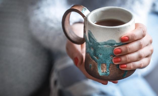 Menina segurando uma xícara de chá nas mãos Foto gratuita