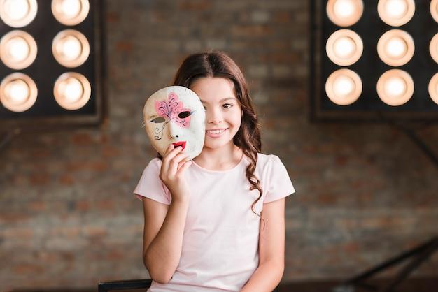 Menina, segurando, veneziano, máscara, em, dela, mãos, frente, fase, luz Foto gratuita