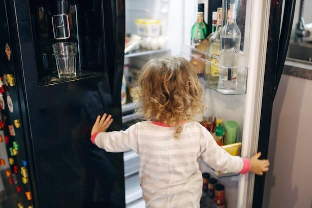 Menina sem rosto, olhando para dentro da geladeira Foto gratuita