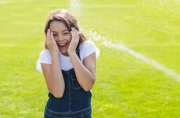 Menina sendo regada com uma pistola de água Foto gratuita