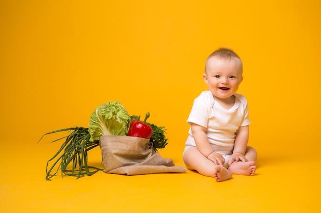 Menina sentada com saco de legumes em amarelo Foto Premium