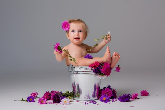 Menina sentada em um balde de flores Foto Premium