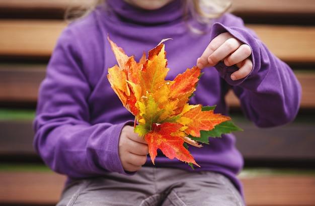 Menina sentada em um banco no parque e segurando nas mãos um buquê de folhas coloridas de outono. Foto Premium