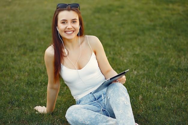 Menina sentada em um campus universitário usando um tablet Foto gratuita