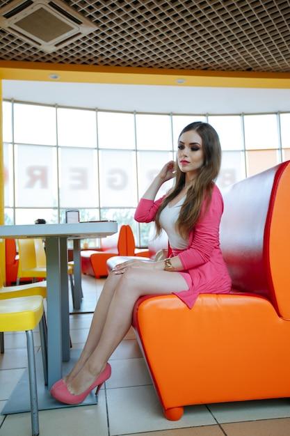 Menina sentada em um restaurante com um assento de laranja Foto gratuita