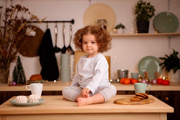 Menina sentada na cozinha de natal na mesa Foto Premium