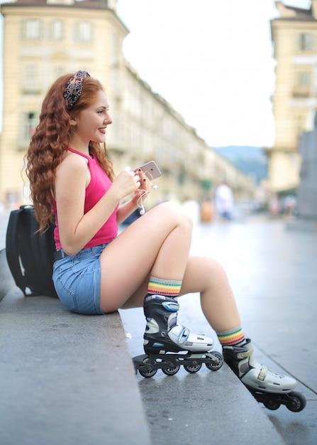 Menina sentada na rua, usando patins Foto Premium