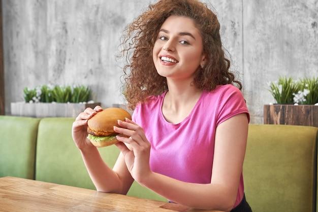 Menina sentada no café, segurando o saboroso hambúrguer, sorrindo. Foto Premium