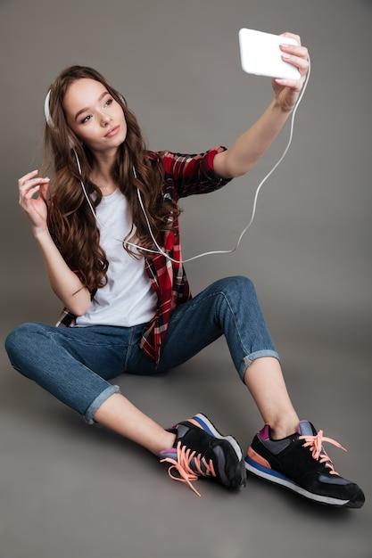 Menina sentada no chão e tomando selfie com fones de ouvido Foto gratuita