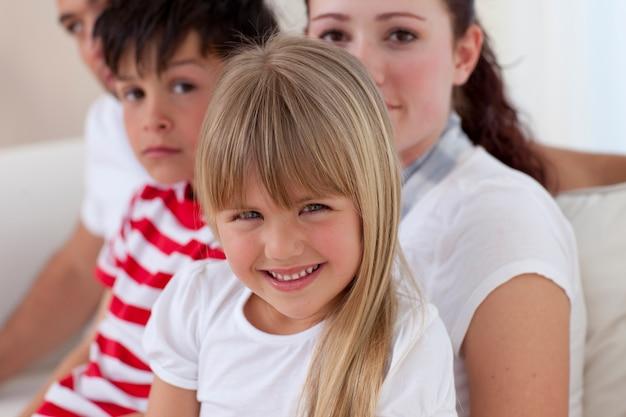 Menina sentada no sofá com sua família Foto Premium