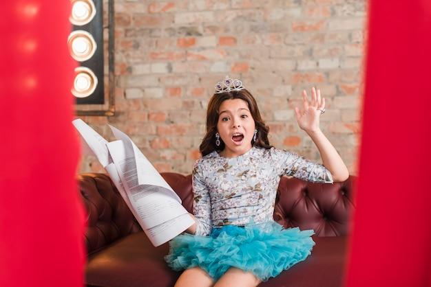 Menina sentada no sofá segurando scripts ensaiando Foto gratuita