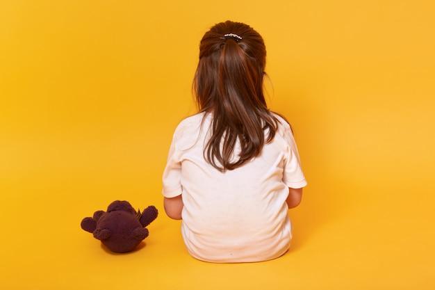 Menina sentada para trás com ursinho marrom Foto gratuita