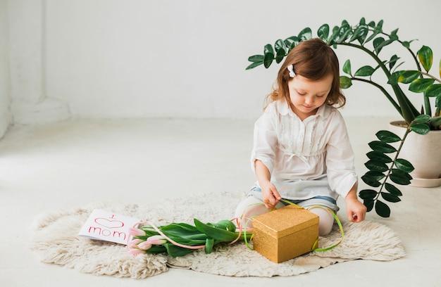 Menina, sentando, com, caixa presente, e, cartão cumprimento Foto gratuita