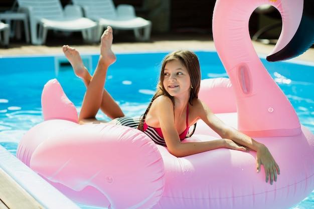 Menina, sentando, ligado, um, flamingo, floatie, e, olhando Foto gratuita