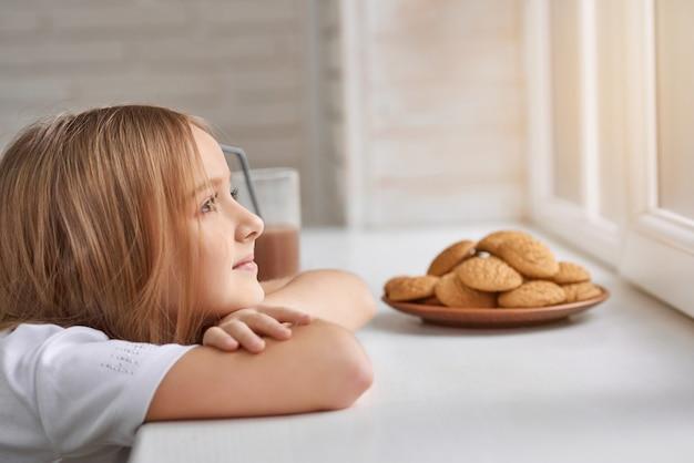 Menina sonhadora com biscoitos no peitoril da janela Foto Premium