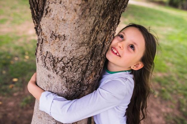 Menina sorridente, abraçando, árvore, em, jardim Foto gratuita