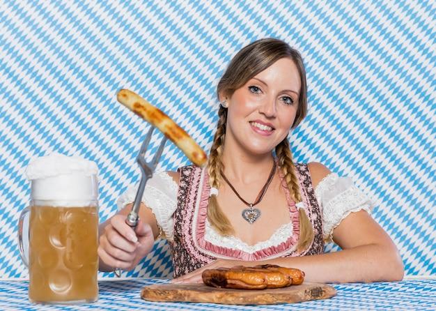 Menina sorridente, apresentando salsichas da baviera Foto gratuita