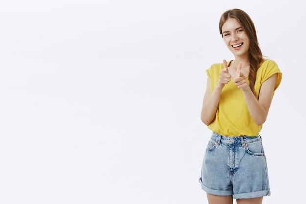 Menina sorridente atrevida apontando os dedos, você conseguiu esse gesto, elogiando a boa escolha Foto gratuita