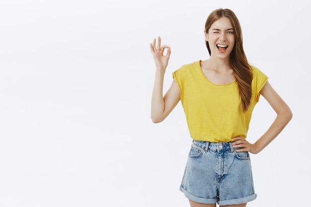 Menina sorridente atrevida mostrando um gesto de aprovação, gosto de ideia, garantia de qualidade Foto gratuita