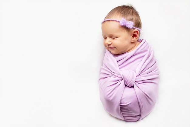 Menina sorridente bebê recém-nascido está dormindo no fundo branco Foto Premium