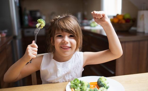 Menina sorridente brincando com comida Foto gratuita