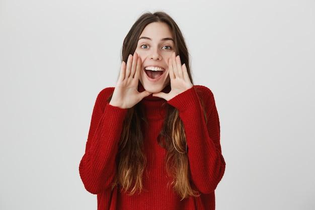 Menina sorridente chamando você, gritando em voz alta Foto gratuita