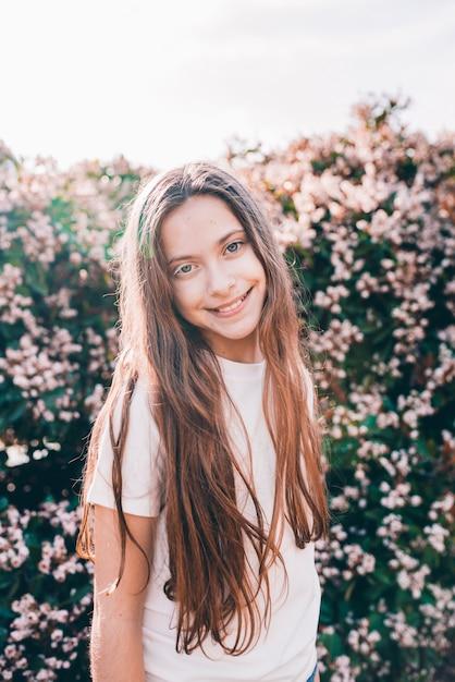 Menina sorridente com cabelos longos, olhando para a câmera Foto gratuita