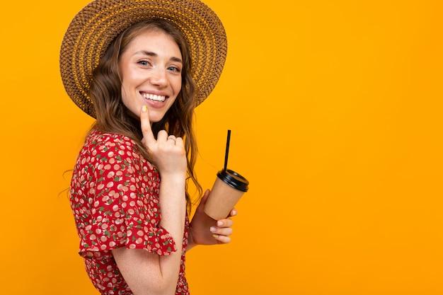 Menina sorridente com café em um amarelo em um vestido vermelho Foto Premium