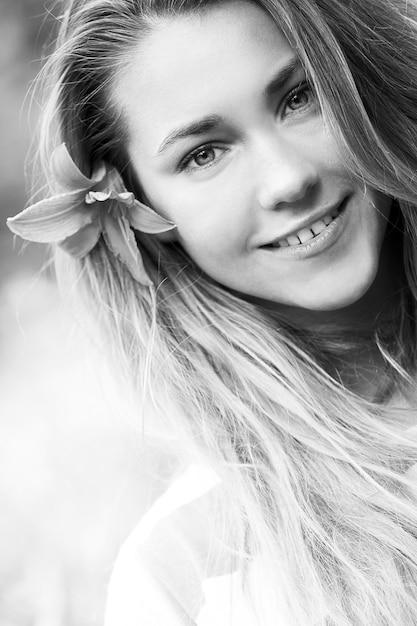 Menina sorridente com flor de lírio no cabelo Foto gratuita