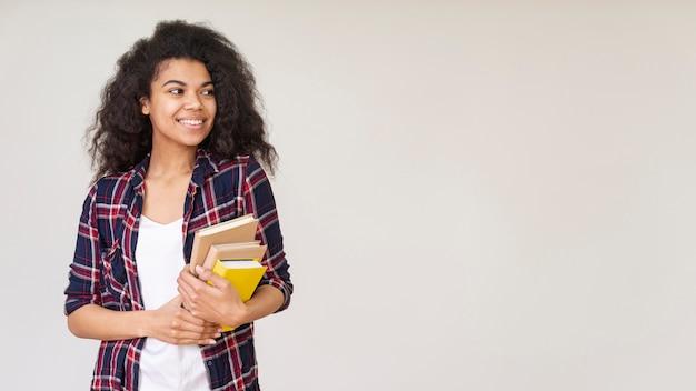 Menina sorridente com pilha de livros Foto gratuita