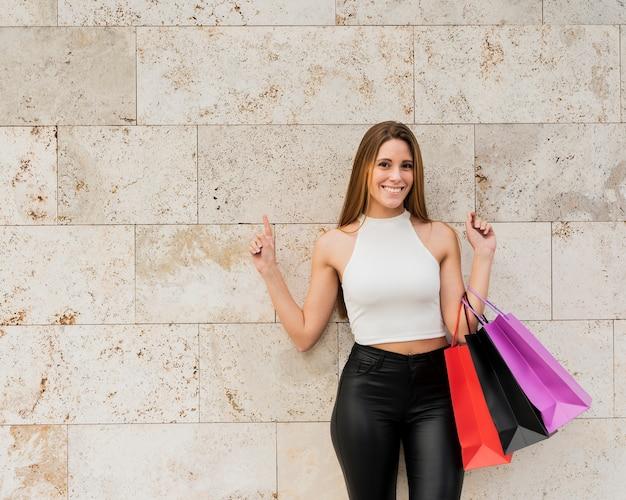 Menina sorridente com sacos de compras em pé junto à parede Foto gratuita