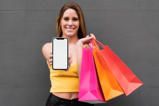 Menina sorridente com sacos de compras, segurando o telefone Foto gratuita
