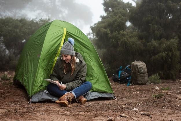 Menina sorridente completo tiro sentado perto da tenda Foto gratuita