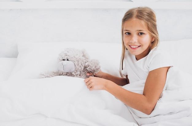 Menina sorridente de alto ângulo, ficar na cama com seu ursinho de pelúcia Foto gratuita