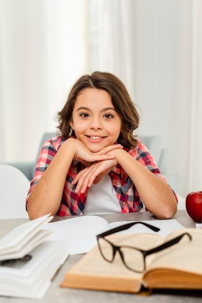 Menina sorridente de alto ângulo no intervalo do estudo Foto gratuita