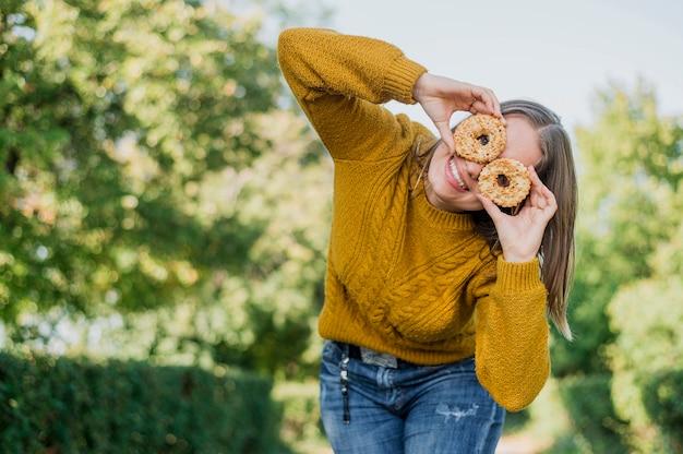 Menina sorridente de baixo ângulo com donuts ao ar livre Foto gratuita