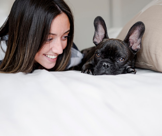 Menina sorridente de close-up com seu bulldog francês Foto gratuita