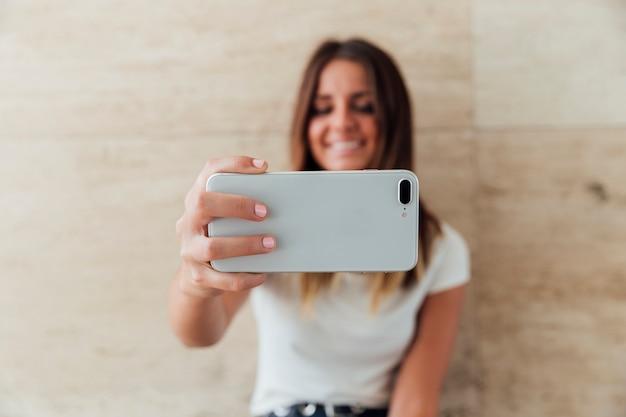 Menina sorridente de close-up tomando uma selfie Foto Premium