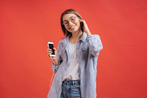 Menina sorridente em roupas casuais e fones de ouvido dançando mãos em movimento. Foto gratuita