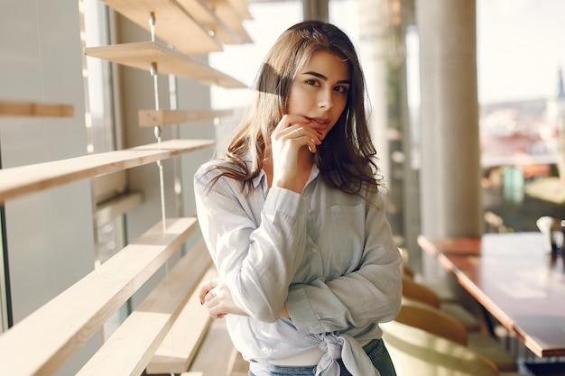 Menina sorridente em uma camisa azul em pé perto da janela Foto gratuita