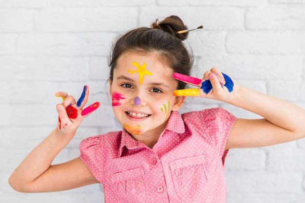 Menina sorridente fazendo gesto de paz com os dedos pintados e rosto contra a parede de tijolos brancos Foto gratuita