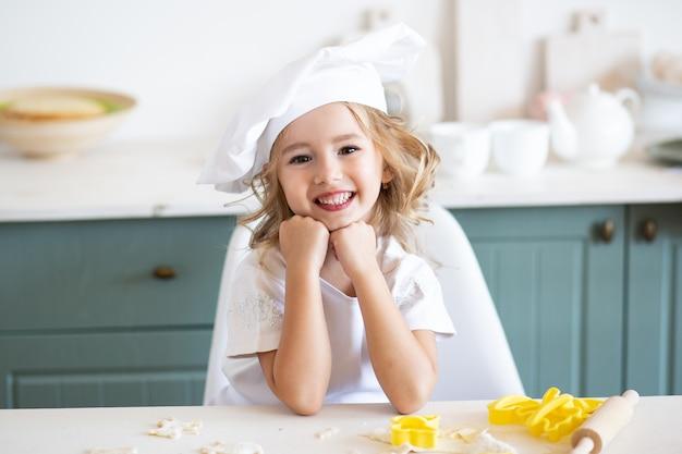 Menina sorridente feliz em um toque de chefs na cozinha Foto Premium