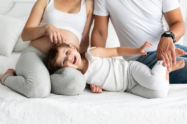 Menina sorridente, ficar na cama com os pais dela Foto gratuita