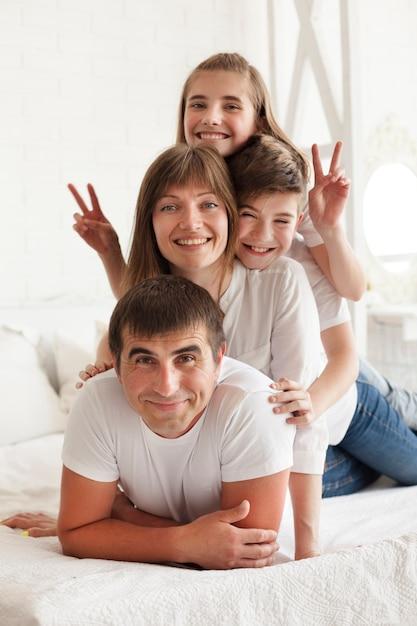Menina sorridente, gesticulando sinal de vitória na cama com seu pai e irmão Foto Premium