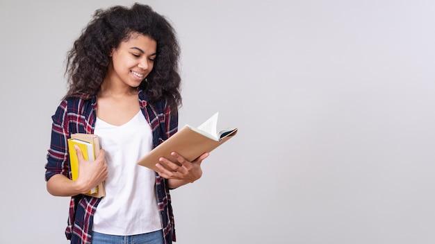 Menina sorridente lendo com cópia-espaço Foto gratuita