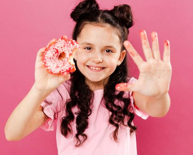 Menina sorridente, mostrando a mão vitrificada de donut Foto gratuita