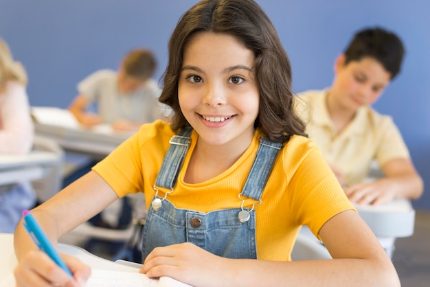 Menina sorridente na escrita da escola Foto gratuita
