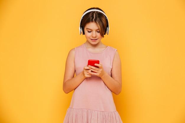 Menina sorridente ocupada usando smartphone e fones de ouvido isolados Foto gratuita